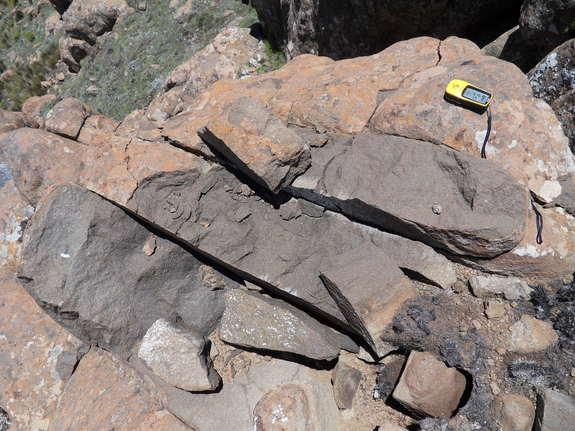 Evidence of a lighting strike hitting rocky mountain summits includes fresh surfaces and blasted rocks.
