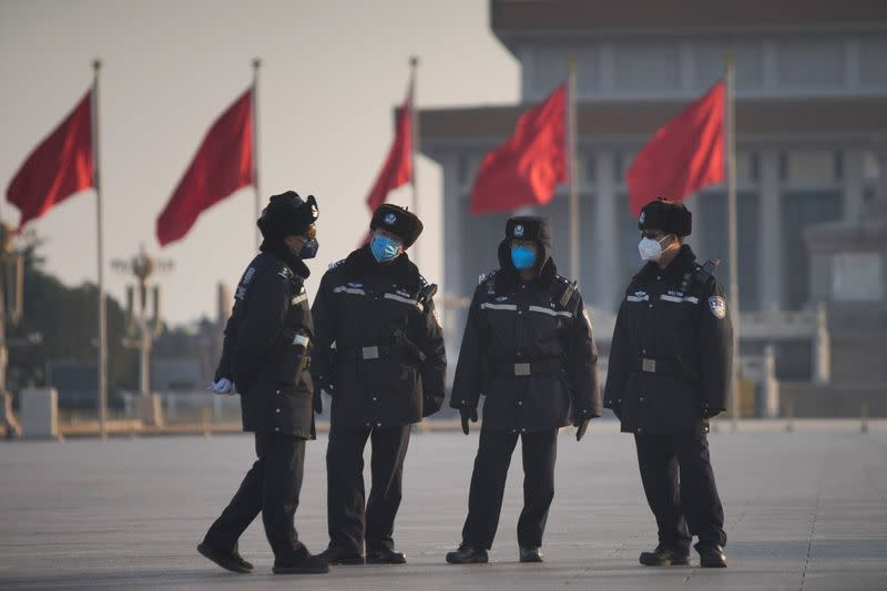 Police officers wearing masks are seen at at the Tiananmen Square, as the country is hit by an epidemic of the new coronavirus, in Beijing