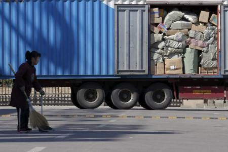 FILE PHOTO: A woman sweeps in front of a truck loaded with parcels at a YTO Express logistic centre in Beijing