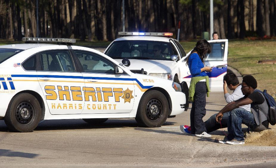 Students wait outside an entrance to the Lone Star College North Harris campus after a shooting on campus on Tuesday, Jan. 22, 2013 in Houston. The shooting wounded three people and sent students fleeing for safety as officials placed the campus on lockdown, officials said. Harris County Sheriff's Maj. Armando Tello said authorities had detained a person of interest. Police did not provide any details about the people who were wounded. (AP Photo/Patric Schneider)