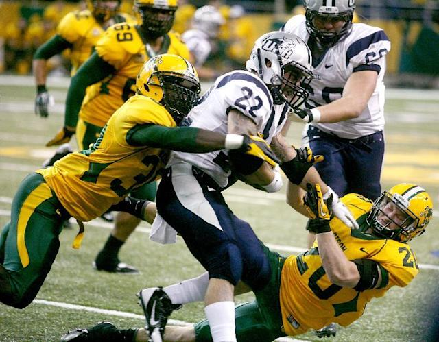 North Dakota State defender Colten Heagle (20) pulls down New Hampshire's Nico Steriti during the first half of an NCAA Football Championship Subdivision semifinal game on Friday, Dec. 20, 2013, at the Fargodome in Fargo, N.D. (AP Photo/Bruce Crummy)