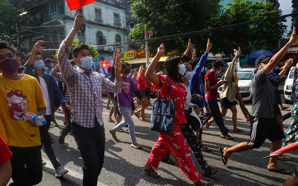 Protesters make the three-finger salute during a demonstration against the military coup in downtown Yangon - STR/AFP