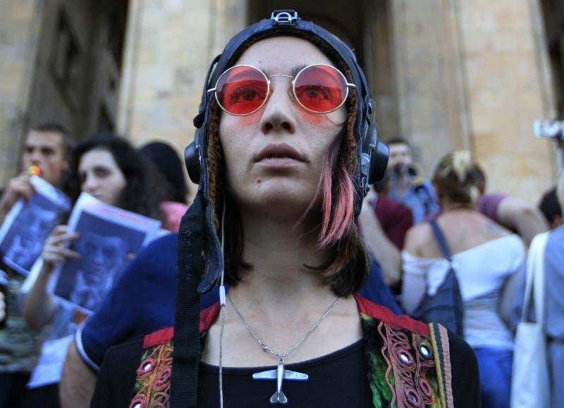 An opposition demonstrator attends a rally in front of the Georgian Parliament building in Tbilisi, Georgia, Monday, June 24, 2019. Demonstrators have returned to parliament for daily rallies, demanding the release of detained protesters, the ouster of the nation's interior minister and changes in the electoral law to have legislators chosen fully proportionally rather than the current mix of party-list and single-mandate representatives. (AP Photo/Shakh Aivazov)