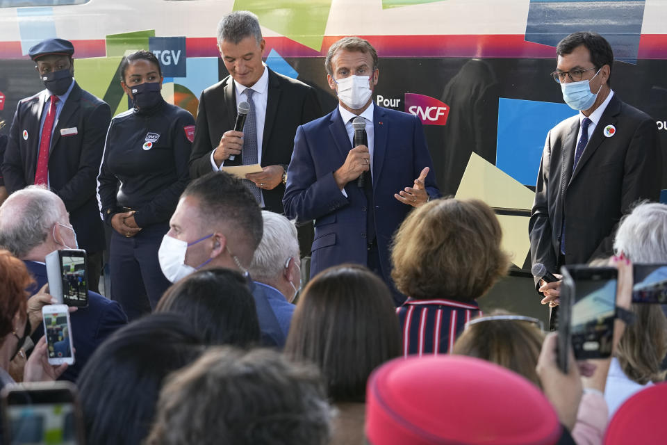"""French President Emmanuel Macron speaks next to French railway operator SNCF CEO Jean-Pierre Farandou, right, at the Gare de Lyon station Friday, Sept. 17, 2021 in Paris. France unveils a super-fast, climate-friendly train of the future, the next generation of its renowned high-speed TGV trains that have been emulated around the world. French President Emmanuel Macron and other government officials are holding a ceremony at the historic Gare de Lyon train station in Paris to mark 40 years since the unveiling of the first TGV, or """"train a grand vitesse."""" (AP Photo/Michel Euler, Pool)"""