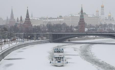 Icebraker floats on Moskva river past Moscow Kremlin during heavy snowfall in Moscow