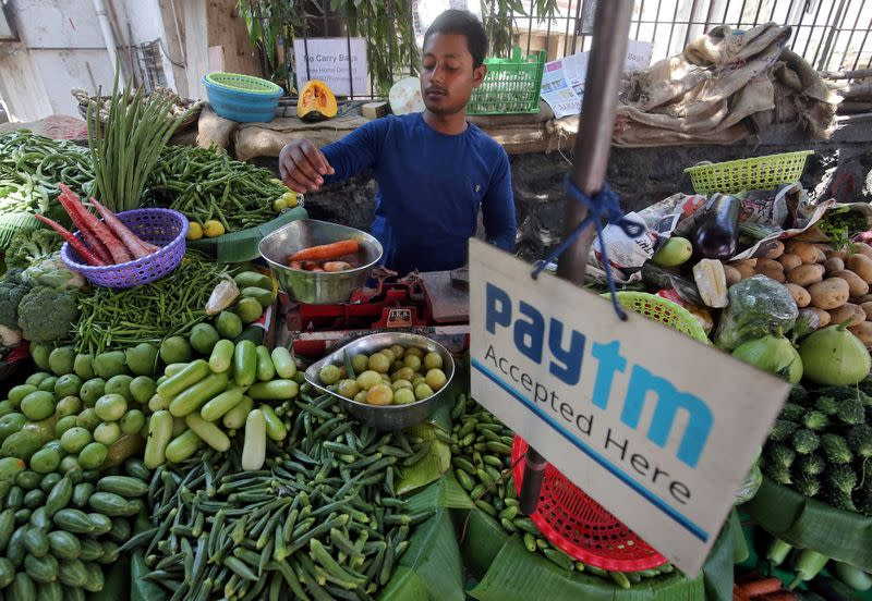 FILE PHOTO: A vendor weighs vegetable next to an advertisement of Paytm, a digital payments firm, hanging amidst his vegetables at a roadside market in Mumbai