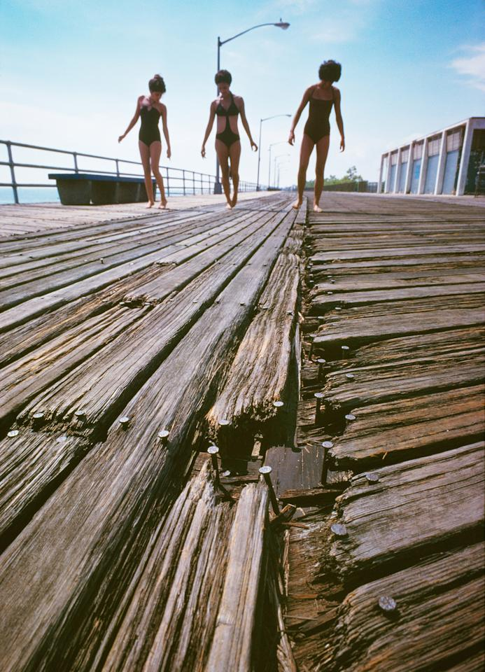 <p>Girls on splintered boardwalk, South Beach, Staten Island. (Photograph by Neal Boenzi/NYC Parks Photo Archive/Caters News) </p>