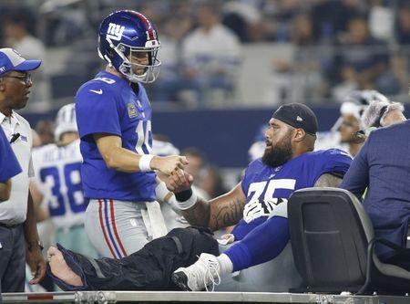 Sep 16, 2018; Arlington, TX, USA; New York Giants quarterback Eli Manning (10) talks to offensive guard Jon Halapio (75) as he is carted off the field after being injured in the third quarter against Dallas Cowboys at AT&T Stadium. Mandatory Credit: Tim Heitman-USA TODAY Sports