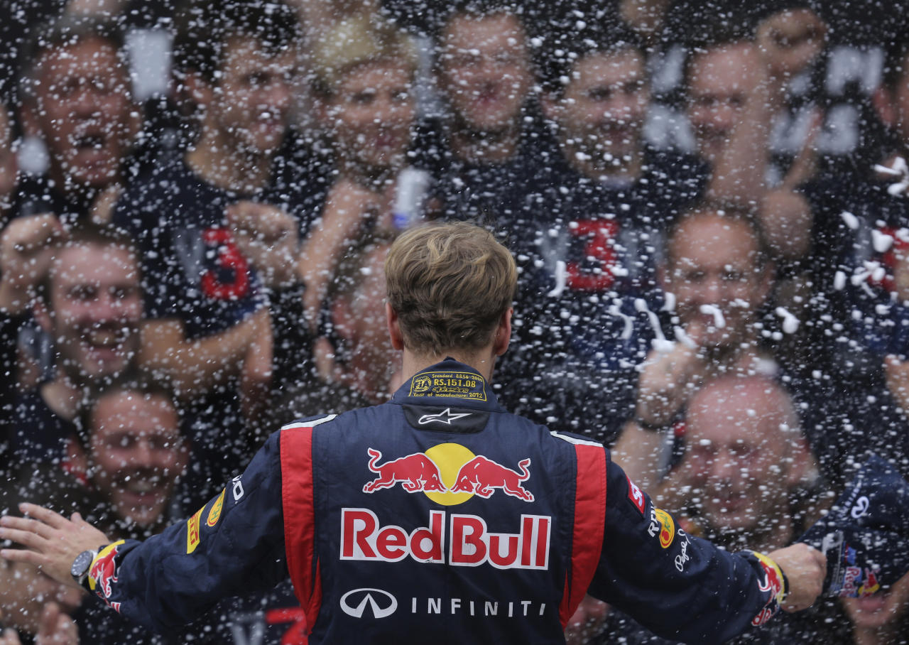 Red Bull Formula One driver Sebastian Vettel of Germany celebrates winning the world championship on the podium with his team after the Brazilian F1 Grand Prix at Interlagos circuit in Sao Paulo November 25, 2012. Vettel became Formula One's youngest triple world champion at the age of 25 at the Brazilian Grand Prix on Sunday.  REUTERS/Ricardo Moraes (BRAZIL  - Tags: SPORT MOTORSPORT SPORT MOTORSPORT F1 TPX IMAGES OF THE DAY)