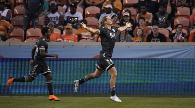 Vancouver Whitecaps's Brek Shea, right, celebrates with Yordi Reyna, left, after scoring a goal along during the second half of an MLS soccer game against the Houston Dynamo Saturday, March 10, 2018, in Houston. (AP Photo/David J. Phillip)