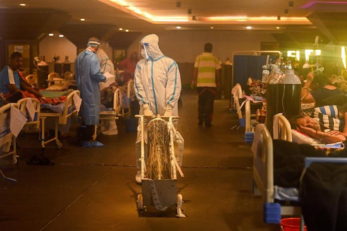 Health workers wearing personal protective equipment attend to COVID-19 patients inside a banquet hall temporarily converted into a covid care center in New Delhi, India on Wednesday.
