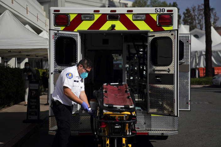 An EMT disinfects a gurney after transporting a patient at St. Joseph Hospital in Orange, Calif., Thursday, Jan. 7, 2021. California health authorities reported Thursday a record two-day total of 1,042 coronavirus deaths as many hospitals strain under unprecedented caseloads (AP Photo/Jae C. Hong)