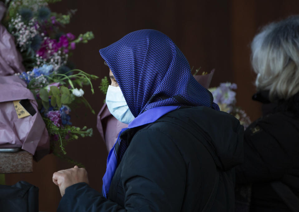 An Iranian woman gathers flowers to hand to lawyers during the trial of four persons, including an Iranian diplomate and Belgian-Iranian couple at the courthouse in Antwerp, Belgium, Thursday, Feb. 4, 2021. An Iranian official on Thursday was convicted of masterminding a thwarted bomb attack against an exiled Iranian opposition group in France in 2018 and sentenced to 20 years in prison by a Belgian court that rejected his claim of diplomatic immunity. Assadollah Assadi, a Vienna-based diplomat detained in Belgium, refused to testify during his trial last year, invoking his diplomatic status. He did not attend Thursday's hearing at the Antwerp courthouse. (AP Photo/Virginia Mayo)