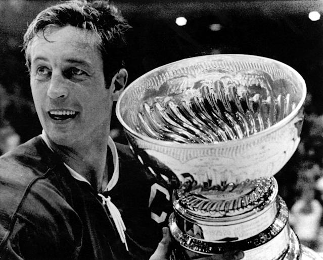 FILE - In this May 19, 1971, file photo, Montreal Canadiens team captain Jean Beliveau holds the Stanley Cup in Chicago following the Canadiens 3-2 victory over the Chicago Blackhawks. Beliveau died Tuesday, Dec. 2, 2014. He was 83. The team confirmed the death of the Hall of Fame center and one of the most beloved players in Canadiens history. (AP Photo/File)
