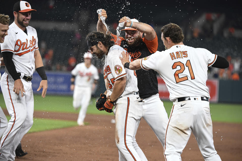 Baltimore Orioles pour water onto Ryan McKenna (65) after he drew a bases-loaded walk to drive in the winning run against the Miami Marlins in the ninth inning of a baseball game Wednesday, July 28, 2021, in Baltimore. (AP Photo/Terrance Williams)