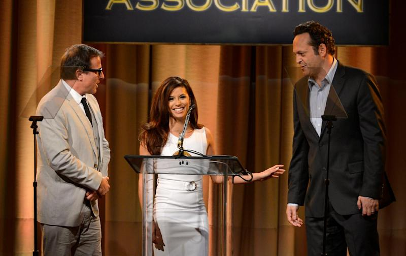 From left, David O. Russell, Eva Longoria and Vince Vaughn speak on stage at the Hollywood Foreign Press Association Luncheon at the Beverly Hilton Hotel on Tuesday, Aug. 13, 2013, in Beverly Hills, Calif. (Photo by Chris Pizzello/Invision/AP)