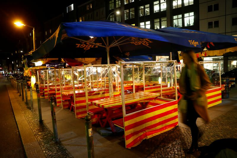 A woman walks past empty tables of a restaurant, in Berlin's Mitte district