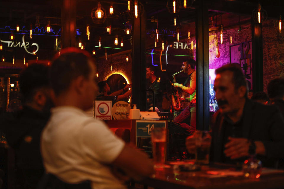 Musicians perform at a bar in Istanbul, Turkey, Friday, Oct. 23, 2020. In much of Europe, city squares and streets, be they wide, elegant boulevards like in Paris or cobblestoned alleys in Rome, serve as animated evening extensions of drawing rooms and living rooms. As Coronavirus restrictions once again put limitations on how we live and socialize, AP photographers across Europe delivered a snapshot of how Friday evening, the gateway to the weekend, looks and feels. (AP Photo/Emrah Gurel)