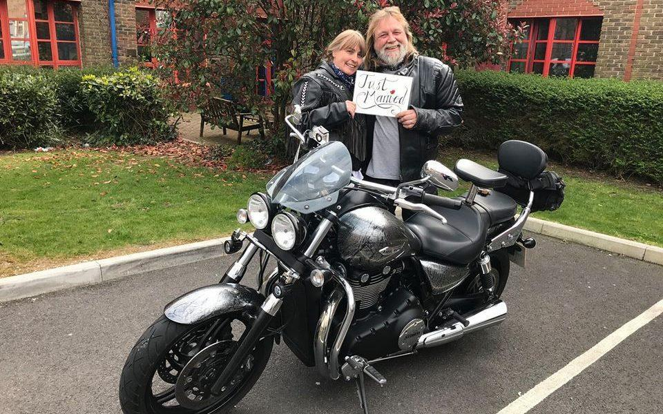 Tina and Mick Hickman pose with 'Just Married' sign behind motorcycle - Dorset County Hospital NHS Foundation Trust Facebook page