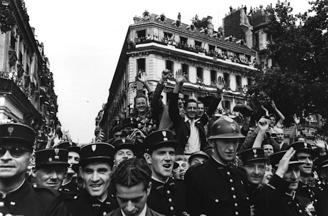 "<p>Crowds fill up the Champs-Élysées on Aug. 26, 1944, to celebrate the liberation of Paris in France. ""I would say that the war correspondent gets more drinks, more girls, better pay, and greater freedom than the soldier, but at this stage of the game, having the freedom to choose his spot and being allowed to be a coward and not be executed for it is his torture."" (© Robert Capa/International Center of Photography/Magnum Photos) </p>"