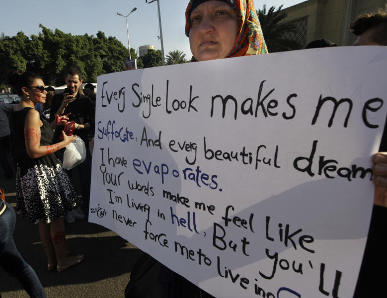 FILE - In this June 14, 2014 file photo, an Egyptian woman holds a banner during a protest against sexual harassment in Cairo, Egypt. A video posted on Facebook Aug. 15, 2018, by an Egyptian woman who says a man stalked her at a bus stop has stirred online debate, with many -- including women -- taking the man's side. Some say he was politely flirting and the woman overreacted, while others have speculated about what she was wearing, suggesting she was the one at fault. The diverging responses point to the difficulty in combatting the rampant sexual harassment on Egypt's streets. (AP Photo/Amr Nabil, File)