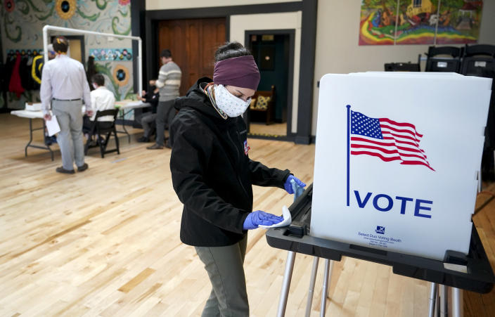 Shanon Hankin cleans a voter booth after it was used at the Wil-Mar Neighborhood Center in Madison, Wis., on April 7. (Steve Apps/Wisconsin State Journal via AP)
