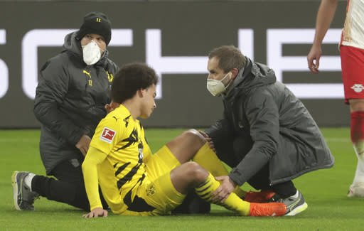 Dortmund's Axel Witsel receives medical attention during the German Bundesliga soccer match between RB Leipzig and Borussia Dortmund in Leipzig, Germany, Saturday, Jan. 9, 2021. (AP Photo/Michael Sohn)