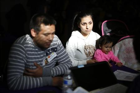 Enrique Gonzalez, 22, Janet Regalado, 21, and their nine-month-old daughter Kayleen Gonzalez pose for a photo after signing up for health insurance at an enrollment event in Commerce