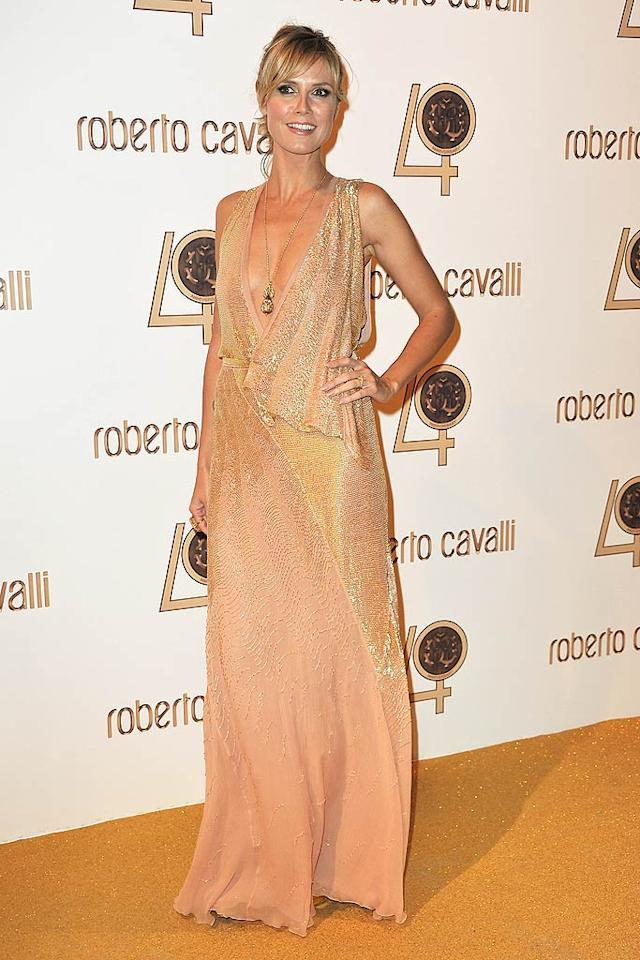 """""""Project Runway's"""" Heidi Klum was gorgeous as usual in a revealing, shimmery number as she presented Cavalli with a giant, sparkler-festooned cake that towered over both of them. """"You have such a vision, and you make us look beautiful,"""" the supermodel said. Pascal Le Segretain/<a href=""""http://www.gettyimages.com/"""" target=""""new"""">GettyImages.com</a> - September 29, 2010"""