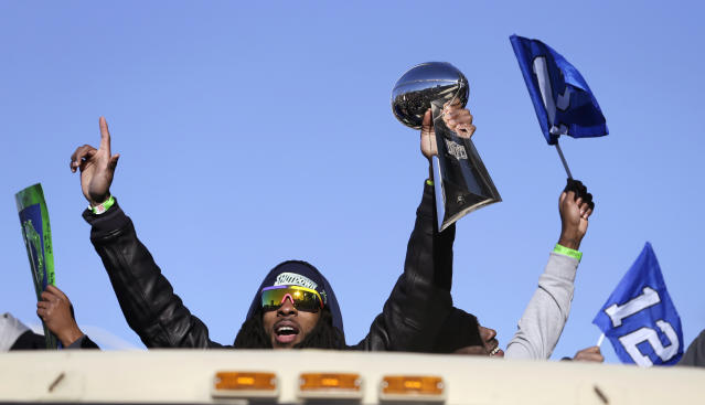 Seattle Seahawks' Richard Sherman holds up the Vince Lombardi Trophy during a parade for the NFL football Super Bowl champions Wednesday, Feb. 5, 2014, in Seattle. The Seahawks defeated the Denver Broncos 43-8 on Sunday. (AP Photo/Elaine Thompson)