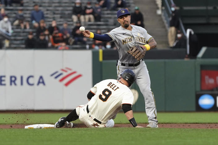 Milwaukee Brewers second baseman Jace Peterson, top, throws to first base after forcing out San Francisco Giants' Brandon Belt (9) at second base on a double play hit into by Buster Posey during the first inning of a baseball game in San Francisco, Wednesday, Sept. 1, 2021. (AP Photo/Jeff Chiu)