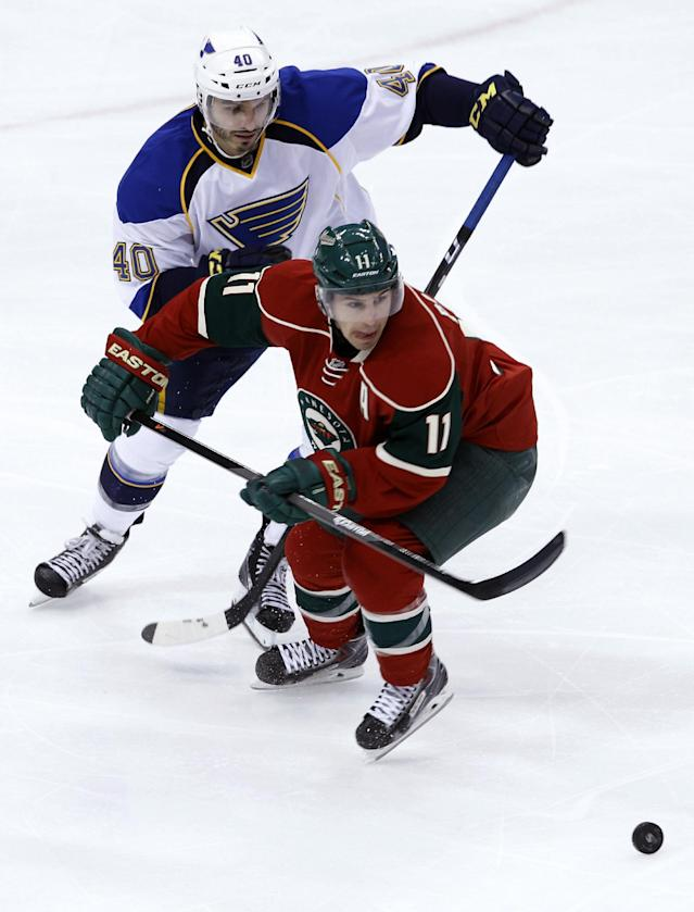 Minnesota Wild left wing Zach Parise (11) and St. Louis Blues center Maxim Lapierre (40) chase the puck during the first period of an NHL hockey game in St. Paul, Minn., Thursday, April 10, 2014. (AP Photo/Ann Heisenfelt)