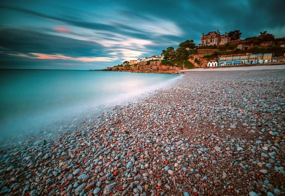 <p>A contrast of turquoise colours echoes underneath the cloudy sky in this image of a pebble covered beach in Brixham, Devon. (Image: Nigel Martin) </p>