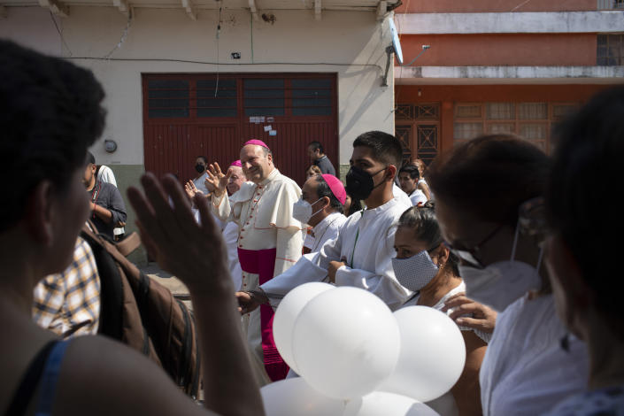 Monsignor Franco Coppola, the Vatican's diplomat to Mexico, greets people as he arrives to meet families and celebrate Mass in Aguililla, a town that has been cut off by warring cartels in Michoacan state, Mexico, Friday, April 23, 2021. State police and soldiers were sent in to restore order earlier this month, but cartels responded by parking hijacked trucks across roads to block them, as well as digging deep trenches across roadways. (AP Photo/Armando Solis)