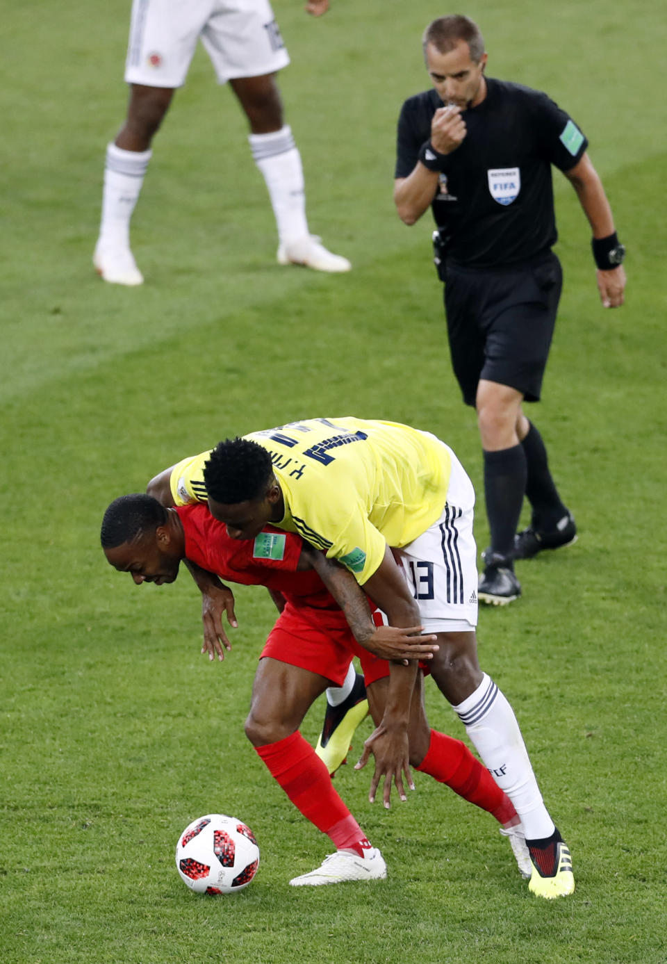 <p>Referee Mark Geiger watches England's Raheem Sterling try and hold on to the ball with Colombia's Yerry Mina on his back </p>