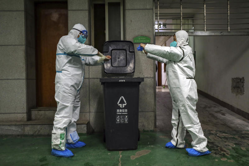 FILE - In this Sunday, Jan. 26, 2020, file photo, ambulance crew members dispose of protective gear in Wuhan in central China's Hubei Province. As Beijing instates one of the largest quarantines in modern history, locking down over 50 million people in Hubei province, questions are swirling around the provincial government's sluggish initial response. (Chinatopix via AP, File)