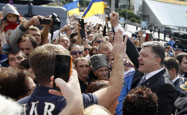 Ukrainian President Petro Poroshenko raises his fist in front of the audience during a military parade marking the 23rd anniversary of Ukraine's independence in the center of Kiev on August 24, 2014