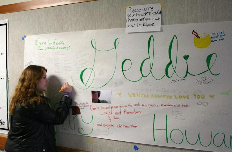 In this photo provided by the Arcata High School Pepperbox, Arcata High School student Blaire Floyd writes on a poster memorial for fellow student Gregory Kulijan Monday, Nov. 26, 2012, at Arcata High School in Arcata, Calif. The Kuljian family were out for a walk Saturday, Nov. 24 at Big Lagoon beach, playing fetch with their dog when Gregory Kuljian tossed a stick that took their dog down to the water's edge. Kuljian's son ran to save the dog, and struggled as he was captured by the surging surf. Howard Kuljian followed, and later his wife. Both parents' bodies were later recovered, but the boy, presumed dead, is still missing. (AP Photo/Courtesy Forrest Lewis, Arcata High School Pepperbox)