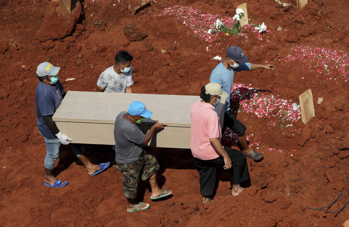Workers carry a coffin for burial at the special section of Jombang Public Cemetery reserved for those who died of COVID-19, in Tangerang, on the outskirts of Jakarta, Indonesia, Wednesday, Aug. 4, 2021. Indonesia surpassed 100,000 confirmed COVID-19 deaths on Wednesday, a grim milestone in a country struggling with its worst pandemic wave fueled by the delta variant, amid concerns the actual figure could be much higher. (AP Photo/Tatan Syuflana)