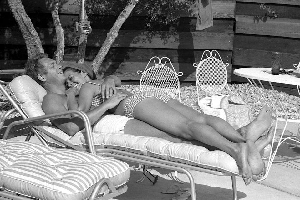 <p>Steve McQueen and his wife Neile Adams lie on a deck chair next to the pool at their Palm Springs, California home in 1963.</p>