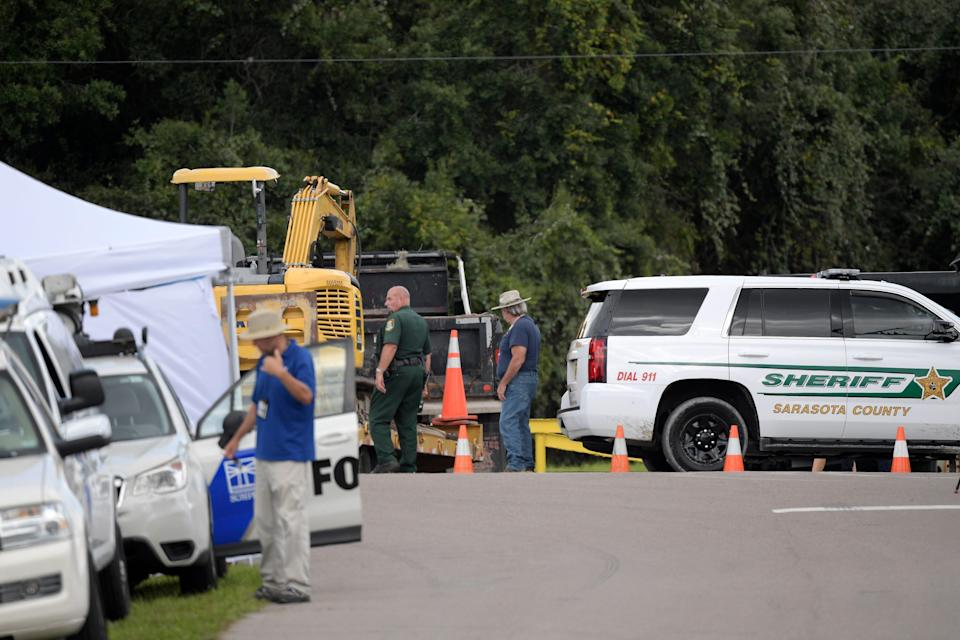 """A Sarasota County Sheriff's Office deputy and a Sarasota County worker direct a truck carrying excavating equipment into the Carlton Reserve during a search for Brian Laundrie, Tuesday, Sept. 21, 2021, in Venice, Fla. Laundrie is a person of interest in the disappearance of his girlfriend, Gabrielle """"Gabby"""" Petito."""
