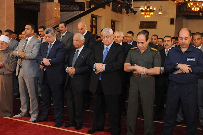 FILE - This Oct. 15, 2013 file photo released by the Egyptian Presidency shows interim President Adly Mansour, center, interim Prime Minister Hazem el-Beblawi, fourth from left, and Defense Minister Gen. Abdel-Fattah el-Sissi, second from right, pray on the first day of Eid al-Aha, or Feast of Sacrifice, in Cairo, Egypt. The head of Egypt's military, Abdel-Fattah el-Sissi, is riding on a wave of popular fervor that is almost certain to carry him to election as president. Unknown only two years ago, a broad sector of Egyptians now hail him as the nation's savior after he ousted the Islamists from power, and the state-backed personality cult around him is so eclipsing, it may be difficult to find a candidate to oppose him if he runs. Still, if he becomes president, he faces the tough job of ruling a deeply divided nation that has already turned against two leaders.(AP Photo/Egyptian Presidency, File)