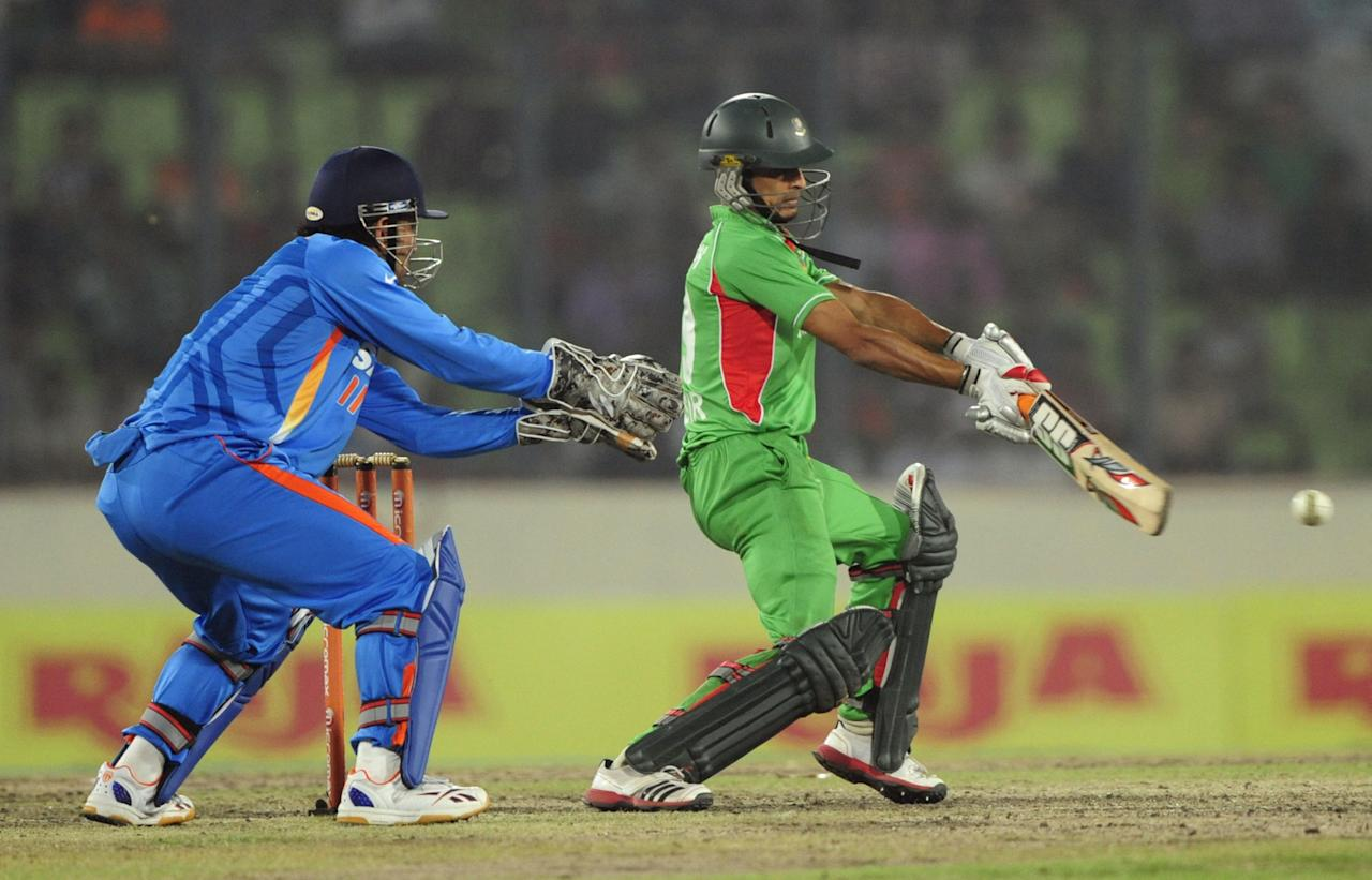 Bangladeshi batsman Nasir Hossain (R) plays a shot as Indian captain Mahendra Singh Dhoni (L) looks on during the one day international (ODI) Asia Cup cricket match between India and Bangladesh at the Sher-e-Bangla National Cricket Stadium in Dhaka on March 16, 2012. India's Sachin Tendulkar became the first batsman in history to score 100 international centuries, adding another milestone in his record-breaking career. AFP PHOTO/Munir uz ZAMAN (Photo credit should read MUNIR UZ ZAMAN/AFP/Getty Images)