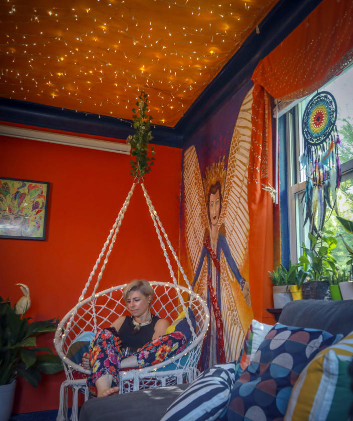 Rachel Berry, who has lived in New York City since 2004, from Laurel, Maryland, sits in a hammock swing in her living room decorated with her artwork, Monday, July 6, 2020, in New York. Before the coronavirus pandemic, Berry worked as a bartender and waited tables, jobs that gave her enough time to work on her creative pursuits. But as New York City tries to reopen, there's concern that jobs for the city's creative class are no longer readily available. (AP Photo/Bebeto Matthews)