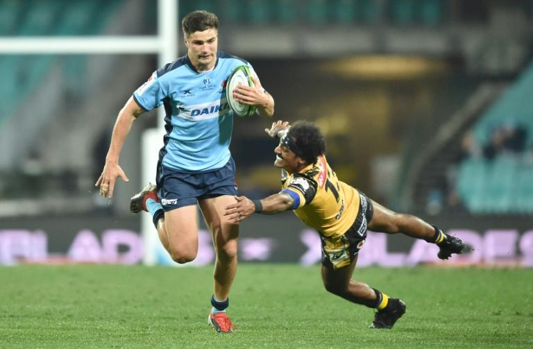 Waratahs' Jack Maddox (L) avoids a tackle by Western Force's Marcel Brache during their Super Rugby match in Sydney