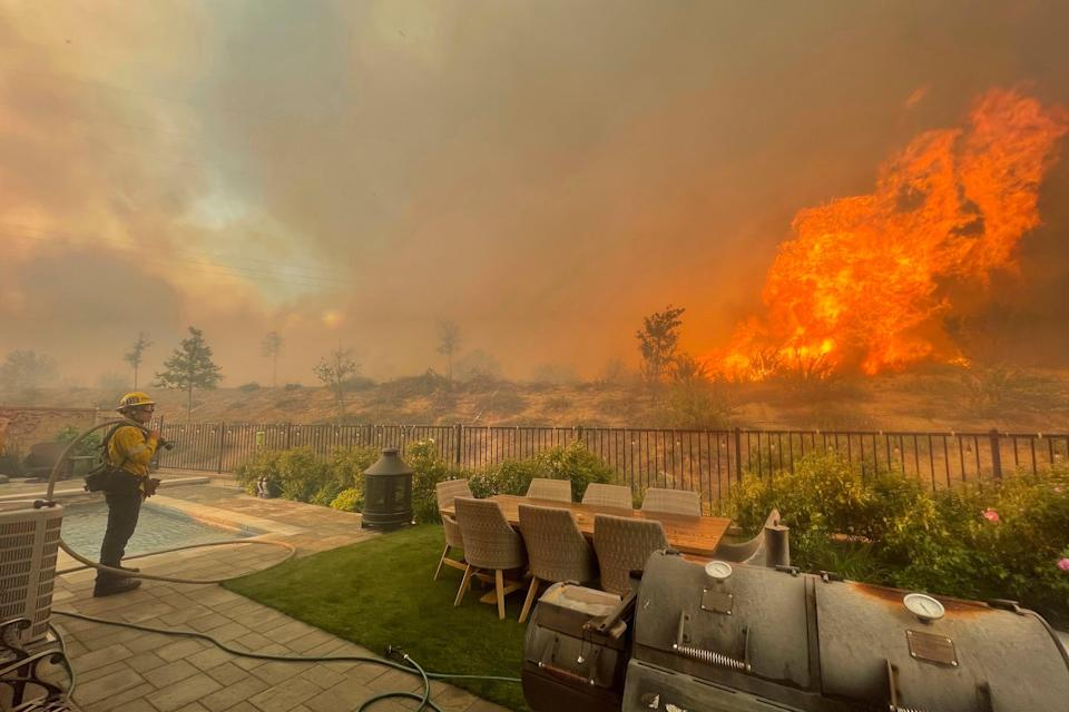 A firefighter prepares to battle the North Fire from a backyard on Via Patina, in Santa Clarita, California earlier this year (AP)