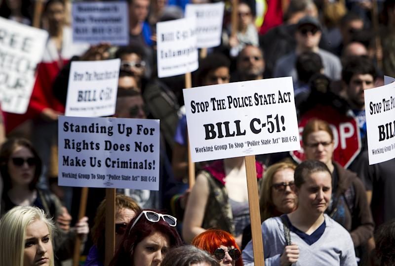 Protesters hold signs during a demonstration against Bill C-51, the Canadian federal government's proposed anti-terrorism legislation in Vancouver.