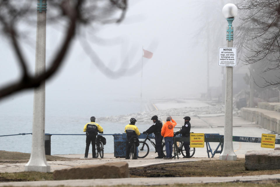 Members of the Chicago Police Department's bicycle patrol wait in the fog at a barricade where a trail along Lake Michigan was closed to all traffic, Thursday, March 26, 2020, in Chicago. (AP Photo/Charles Rex Arbogast)