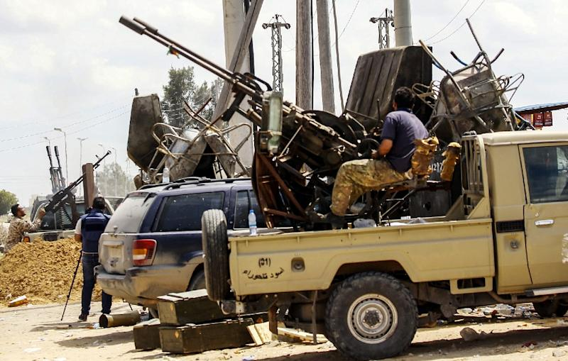 Fighters man vehicle borne guns stationed at a position held by forces loyal to Libya's the unity government in the suburb of Wadi Rabie (AFP Photo/Mahmud TURKIA)