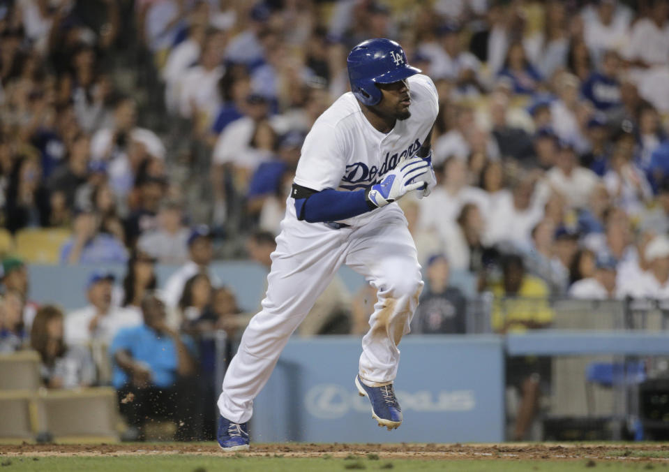 FILE - In this July 29, 2014, file photo, Los Angeles Dodgers' Carl Crawford runs to first base after hitting a RBI single during the fifth inning of the team's baseball game against the Atlanta Braves in Los Angeles. Former Dodgers star Crawford has been arrested after his former girlfriend accused him of assaulting her during an argument over a man she had begun dating. An arrest affidavit filed Wednesday, June 3, 2020, by Houston police states that the ballplayer-turned-record producer went to the home of Gabriele Washington on May 8, produced a handgun from which he unloaded the ammunition in her presence, then demanded information on her latest dating relationship. (AP Photo/Jae C. Hong, File)